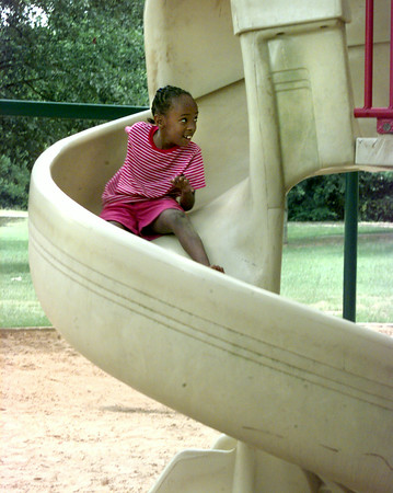 6/24/99-Latoria Thompson, 7, daughter of Melissa Thompson of Longview, takes a ride on the slide at Teague Park Thursday afternoon in Longview. Jessica Williamson