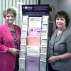 6/22/99-Susan Garner, left, president of the Pilot Club of Longview, and Glenda Burt, senior vice president of Spring Hill Bank and Trust, stand by the new Alzheimer's tree brochure stand recently placed in the lobby of Spring Hill Bank and Trust.  Jessica Williamson