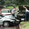 6/22/99-Judy Thompson, left, of Diana, watches as two unidentified men look at the damage done to her Mazada pickup truck after the two car collison on N. Fourth Street. Thompson was coming southbound on N. Fourth St. when she lost control of her vehicle and hit Melissa Turner of Longview who was traveling northbound.  Jessica Williamson
