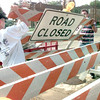 6/3/99---David Deem JR. 17, of Tatum, left, and Randy McDowell, right, of Longview, unload road closed barricades at the intersection of Methvin St. and Center St. Thursday afternoon in Longview. Kevin green