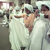 6/22/99--- Camp Harvey members Keisha Rayson, left, and Mayra Vega race to dress themselves in complete surgical attire Tuesday during a visit to Longview Regional Hospital. bahram mark sobhani