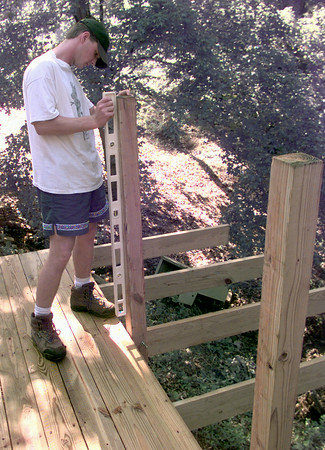 5/8/99---Caleb Pickard the sixteen year old son of Gordon and Enola Pickard of Longview, checks the level as he builds a sixteen by sixty deck for the Hope Haven Womens Ministry for his eagle scout project Saturday morning on Gum Springs outside Longview. kevin green