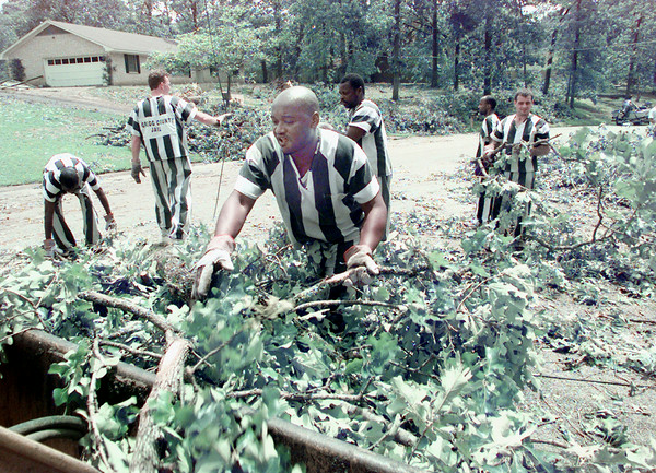 5/5/99---Rodney Wade and other members of the Gregg County Jail's trusties work crew help clean up the debris left in Kilgore from Tuesday's storms. bahram mark sobhani