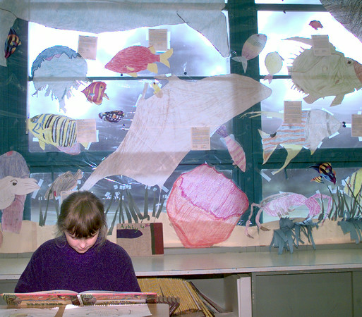 5/25/99---Mozelle Johnston student Angel Fields a fourth grader reads in Donna Ashby's classroom as it is turned into an ocean with fish on the walls and a submarine in the room Tuesday morning in Longview. Kevin green