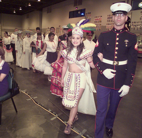 5/8/99---Miss Cinco de Mayo contestant Yadira Montano is escorted by corporal J.C. Grubbs as the contestants make their way to the stage Saturday during the Cinco de Mayo festival at the Maude Cobbe Convention and Activities Center. Montano is wearing an Aztec outfit to represent all of Mexico. bahram mark sobhani