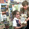 5/12/999Jennifer Weeks, left, gets a little help from St Marys teacher Judy Johnson, right, while showinbg off the wooden shoes her travel buddy got while traveling Tuesday afternoon at St. Mary's in Longview. Kevin green