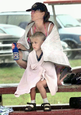 5/31/99---Joe Martin, 6, of Longview, sits with Rhonda Hawthorne, of Marshall, on a pinic table Monday afternoon as rains push people under shelter on the sandy beach at the Lake O The Pines. Kevin Green