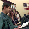 11-23-99---One of the first gradutes of East Texas Christian Charter School Guencho Cerda, left, his mother Sarah Cerda, right, his diploma after graduating Tuesday morning. Cerda will be going into the Army. Kevin Green