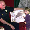11-26-99---LPD police chief A.J. Key gets a little help from Katherine McKay the 3 year old daughter of David and Agnes McKay of Daingerfield, while reading the book The Mitten Saturday afternoon during story time at the Longview Mall. Kevin GReen