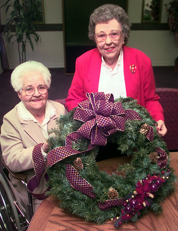 11-2-99---Whispering Pine Lodge residents Callie Ramo, left, and Syble Harris, right, holding a wreath that the resdents will be making for Christmas. Kevin Green