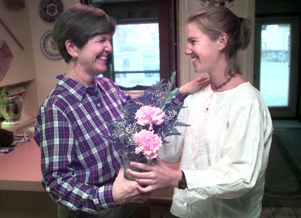 11-23-99---Judy, left, and Kate Hawthorne, right, hold flowers that Kate suprised her mom with after returning from out of the country Tuesday afternoon at thier Home in longview. Kevin GReen