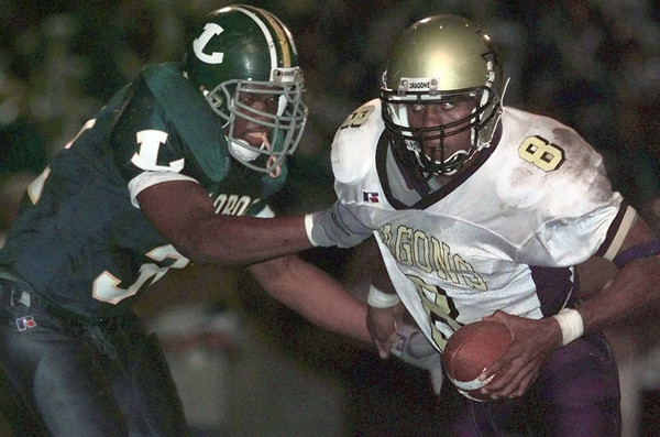 11/5/99---Longview's Marvin Byrdsong tries to bring down Nacogdoches quarterback Rico Harris before Harris pitches the ball in the second quarter of their game at Lobo Stadium. bahram mark sobhani