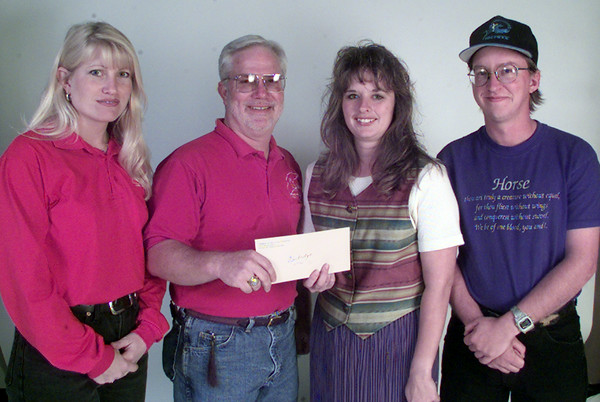11/23/99---Karen Meador, left, and Bull Howard of the Animal Clinic at the Crossings, present a check to Windridge instructors Dawn Searcy and Chris Stow, far right. The money, totalling about $850, was raised at Equifair last month. bahram mark sobhani