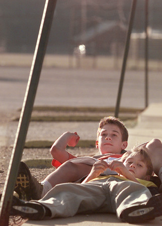 10/6/99---Jarrod Kyle, rear, and his brother Justin lie down on the sidewalk and throw pebbles as they wait for their mom to pick them up Wednesday evening outside Pine Tree Middle School. Jarrod, a seventh grader, had a football game and his brother stayed behind to watch. bahram mark sobhani