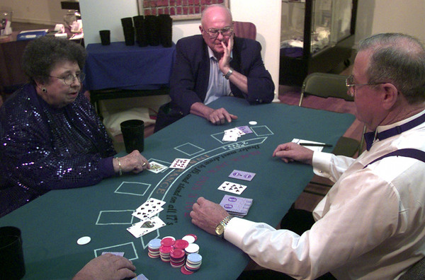 10-23-99---Mavis, left, and VG Rollins, center, gets a few cards from the blackjack dealer Les Wiesner, right, Saturday night during the Casino nights fundraiser at Longview Museum of Fine Arts in downtown Longview. Kevin GReen