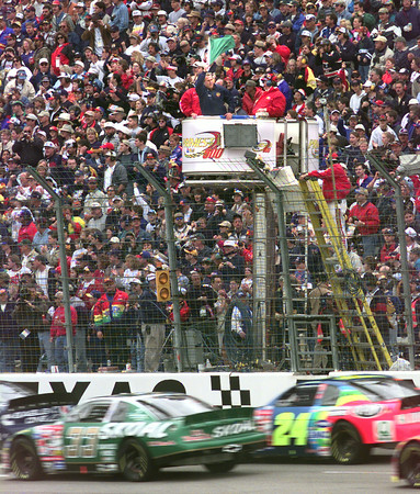 Texas Gov. George W. Bush gives the green flag to NASCAR drivers during the start of the Primestar 500 in Ft. Worth in 99. Kevin Green