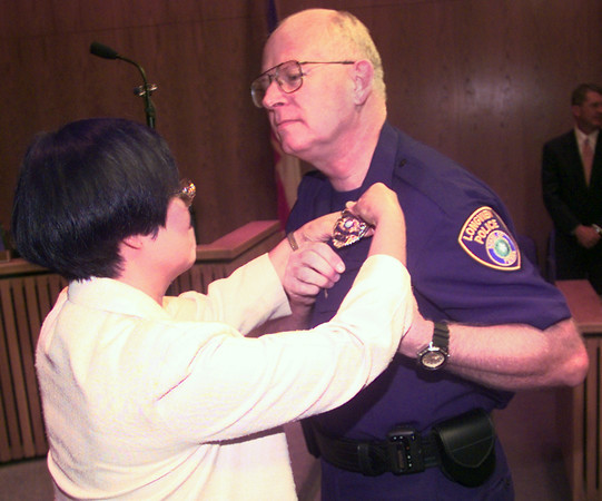 9/2/99---Lee Key, left, pins A. J. 's new badge on as he becomes LPD's new chief of police during a swearing-in Thursday morning at LGV council chambers in LGV. Kevin green