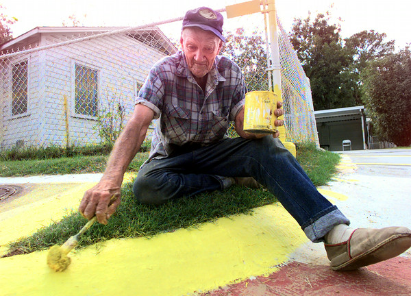 9/9/99---J.B. Richardson, brightens the path around his home with bright yellow paint Thursday afternoon on Senic Dr. in Longview. Darlene