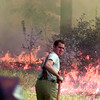 9/14/99---East Mountain firefighter Michael Evans looks for slack in his hose as he fights a brush fire Tuesday north of White Oak near Shiloh Rd. and FM 1845. The fire, which is believed to be caused by a transformer that blew and dropped power lines, scorched brush and trees in a five acre area. White Oak and East Mountain snuffed out the patches of fire with no injuries or property damage. bahram mark sobhani