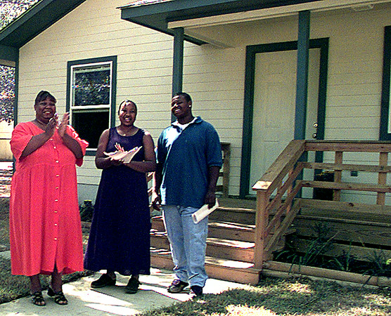 Michelle Hollins left, and daughter Marshinik and son Peter prepair to invite into their new house on 437 Main at the Habitat for Humanity Home Dedication Ceremony Sunday.  ObieLeBlanc 9-19-99