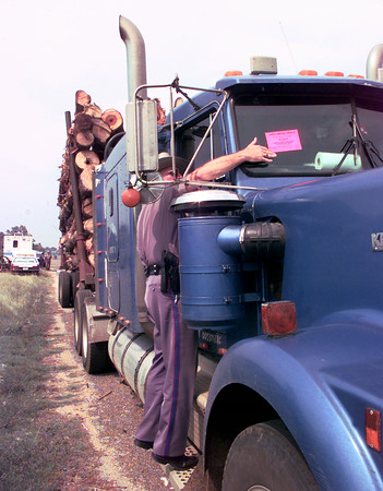 9/3/99---DPS license and weight trooper Buddy Owles red tags an 18-wheeler with an out-of-service tag Friday afternoon for no front brakes during an inspection. Four troopers from four counties were involved in the semi portable scales mobile inspection set up along Texas 149 at whiskey bend outside LGV. Kevin Green