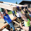 Globe/T. Rob Brown Youth from First United Methodist Church in Elgin, Ill., lift one of several pre-constructed frame pieces Monday morning, June 10, 2013, for Emily Morrison's Joplin home. The youth group is working in conjunction with Rebuild Joplin.