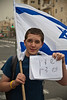 A lone, young, Jewish, anti-protestor holds an Israeli flag and a hand-written sign insinuating the Bedouins are getting what they deserve. Jerusalem, Israel. 29-Apr-2012.