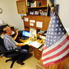 Globe/T. Rob Brown Under the red, white and blue of a flag that belonged to his father, Charlie Bridges of Diamond reviews a Powerpoint presentation he created about his father Walter Bridges, who was a World War I veteran, Monday morning, Aug. 5, 2013.