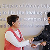 Sharon Clark (right), president of Hope For You, a local breast cancer foundation, receives a donation of $200 collected from a breast cancer fundraising event from Beverly Newman, Mercy Auxiliary Joplin president.<br /> Globe   T. Rob Brown