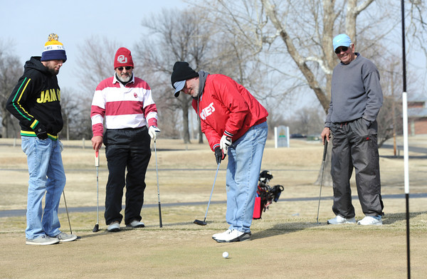 From the left: Year-round golfers Chris Misner,  Karl Moorhead, Jeff Hess and Bob Hamm work on their game despite chilly temperatures and biting wind on Tuesday afternoon at Schifferdecker Golf Course. Globe | Laurie Sisk