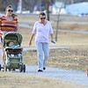 Globe/T. Rob Brown Taking advantage of Friday's warmer temperatures, (from left) Sarah Henry and her 11-month-old son Peyton Gustafson walk with Gustafson's grandmother, Marcia Sherwood and her dog Murphy at Campbell Park in Joplin.