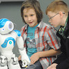 """Trenton Dennis, left and Nathan Striegel, both 11, of Carl Junction work to program their humanoid robot, """"NAO"""" to dance during the Humanoid Robotics competition at a regional technology conference for the Technology Students Association on Friday at Missouri Southern State University. <br /> Globe   Laurie Sisk"""