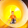 Five-year-old Nolan Houseman of Grove, Okla., slides down playground equipment at Chick-fil-A on  Range Line Road Tuesday afternoon. Houseman was enjoying the warmth of playing indoors. Globe | Laurie Sisk