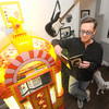 "Lifelong Beatles enthusiast Mark Woodin stands beside his limited edition Yellow Submarine jukebox in his Joplin home while perusing a first edition John Lennon book ""In My Own Write."" Woodin said only about 100 of the jukeboxes were manufactured. Globe 