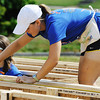 Globe/T. Rob  Brown Emily Baker (right) of Staunton, Va., takes a measurement as Tessa Mandra of Nashua, N.H., looks around, both with Bike & Build, while working on a Habitat for Humanity home in the 2300 block of Joplin Street Tuesday morning, July 23, 2013.