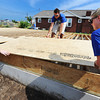 Globe/T. Rob  Brown Claire Kuehnel (left) of North Reading, Mass., and Casey Clark (right) of Philadelphia, Penn., lift a floor board up to Christopher Casey of Berlin, N.J., all with Bike & Build, while working on a Habitat for Humanity home in the 2300 block of Joplin Street Tuesday morning, July 23, 2013.