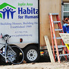 Globe/T. Rob  Brown A lone bicycle rests against a Joplin Area Habitat for Humanity trailer as a group with Bike & Build plan their work strategy for a Habitat for Humanity home in the 2300 block of Joplin Street Tuesday morning, July 23, 2013.