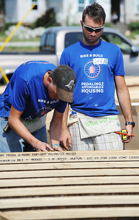 Globe/T. Rob  Brown Shane Flaherty (left) of Las Alamotis, Calif., runs a line to mark board placement as Christopher Casey of Berlin, N.J., looks on, both with Bike & Build, while working on a Habitat for Humanity home in the 2300 block of Joplin Street Tuesday morning, July 23, 2013.
