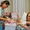 Globe/T. Rob Brown<br /> Johnna Rifenberg of Moberly and newborn daughter, Ryelyne Carmen Rifenberg, receive and show off a princess gift basket from nurse Jennifer Coberley Monday afternoon, July 22, 2013, at Freeman West in honor of the UK royal baby. Ryelyne was the closest baby girl born to the time of the royal baby's birth. A prince gift basket will also be given to the first following baby boy born at Freeman.