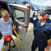 Globe/T. Rob Brown<br /> Zach Beaty, 7, of Webb City, steps foot out of a World War II-era B-17 Flying Fortress bomber, as classmate Colbi Shofler, 8, of Carl Junction, follows, both from the First Baptist Church Learning Center in Carl Junction, Friday morning, June 14, 2013. A group of daycare and preschool students toured the historic aircraft. Monte Constable (right), a Commemorative Air Force load master, holds the door open.