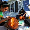 Marisa Ortiz (left) creates a Batman jack-o-lantern as her roommate Erica Gutierrez (center) cuts a raven pattern and her sister Nicole Ortiz creates a vampire pumpkin Saturday afternoon, Oct. 19, 2013, in Pittsburg, Kan. Globe | T. Rob Brown