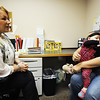 Nine-month-old Brooklin Schoonober reaches up for her mother, Tabatha Schoonober, both of Pittsburg, Kan., as they speak with Krista Smith, registered nurse, Wednesday morning, Oct. 9, 2013, at the Community Health Center of Southeast Kansas in Pittsburg. Globe | T. Rob Brown