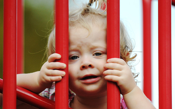 Globe/T. Rob Brown Nineteen-month-old Emma Cameron, plays peek-a-boo between playground equipment bars with her father, Charlie Cameron, while on an outing Friday afternoon, Oct. 12, 2012, to Landreth Park with her father and mother, Leah Cameron, all of Joplin.