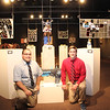 "From left, Patrick Mooney, and Conor McGhehey pose in the Memorial Hall Main Gallery with pieces from their senior thesis art show ""The Altered World."""