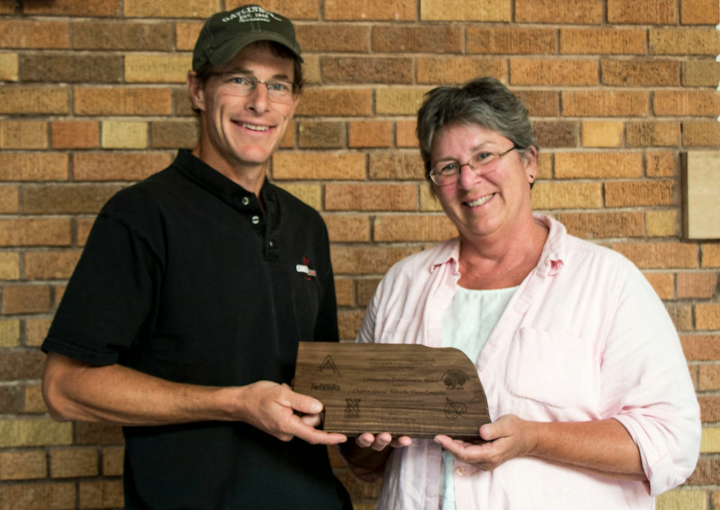Justin Evertson, left, with the Nebraska Statewide Arboretum, presents a plaque to Lucinda Mays, CSC horticulturist, representing the Chadron Greener Nebraska Towns (GNT) Committee which administered a two-and-a-half year grant providing vouchers for about 600 trees and other plantings in the Chadron area. (Tena L. Cook/Chadron State College)