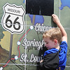 Globe/T. Rob Brown Four-year-old Bryson Snider of Clinton, Okla., gets a boost up to unveil the last state Route 66 sign from Paul Whitehill, owner of Images in Tile which created the murals, during the opening celebration Friday afternoon, Aug. 2, 2013, for the Route 66 International Festival.