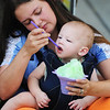 Globe/T. Rob Brown Jessica Brooks shares her snowcone with 8-month-old son Luke Forkner, both of Cherokee, Kan., Friday afternoon, Aug. 2, 2013, during the Route 66 International Festival in downtown Joplin.