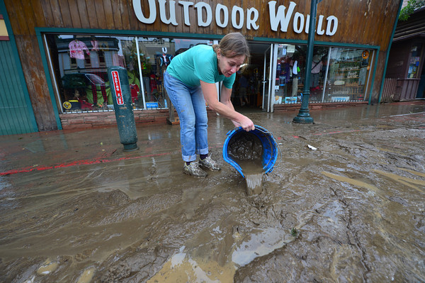 18EPNews Flood Clean Up Begins.jpg Friends and volunteers begin removing mud from Outdoor World on Saturday. Clean up began almost as soon as rain stopped falling, as Estes Park residents and businesses remover mud and debris.