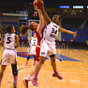 RYAN HUTTON/ Staff photo. Centeral Catholic's Madison Borelli (11) tries to put up a shot over English's Deidra Newson (34) during the first half of Saturday night's game at the Tsongas Center in Lowel.