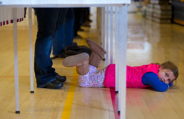 Emma Borrows, 7, waits while her mom Stephanie votes at the polls at Hampstead Middle School.  Photo by Ryan Hutton.